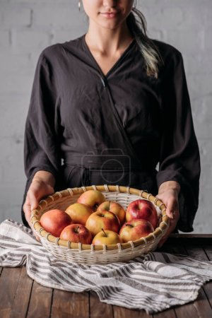 partial view of woman holding basket with fresh apples