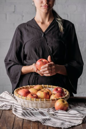 partial view of woman with apple and basket full of fresh apples on wooden tabletop with linen