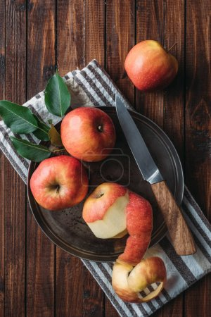 Photo for Flat lay with ripe apples and knife on metal tray on wooden tabletop - Royalty Free Image