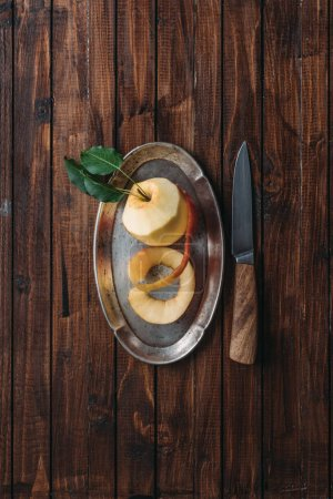 top view of peeled apple on metal tray and knife on wooden tabletop