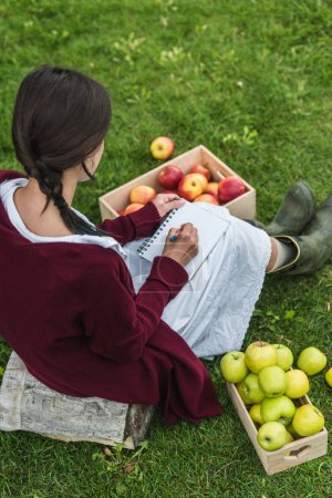 rear view of girl writing in notepad and sitting in garden with wooden boxes of apples