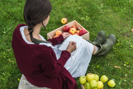 girl writing in notepad in garden with fresh picked apples in wooden boxes