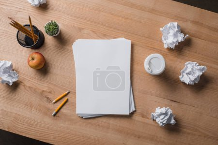 Photo for Top view of stacked blank papers on wooden table with crumpled papers - Royalty Free Image
