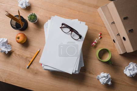 Photo for Top view of stacked blank papers with eyeglasses on top on wooden table - Royalty Free Image