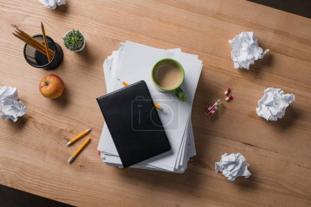 top view of stacked blank papers with cup of coffee and notebook on top on wooden table
