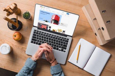 Photo pour Plan recadré de l'homme d'affaires assis sur le lieu de travail avec ordinateur portable, site Web ebay à l'écran - image libre de droit