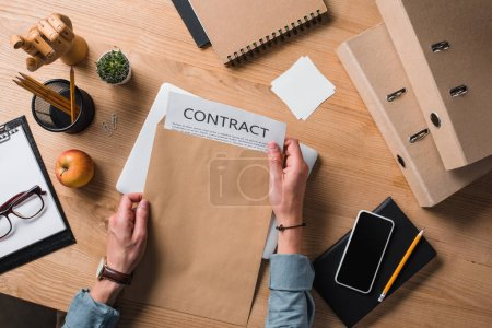 cropped shot of businessman taking contract from envelope at workplace