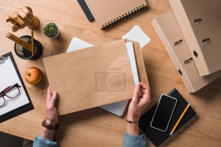 cropped shot of businessman holding envelope with documents at workplace