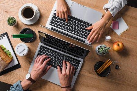 Foto de Recortado de los empresarios que trabajan con ordenadores portátiles en el lugar de trabajo - Imagen libre de derechos