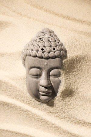 top view of buddha sculpture on sandy beach