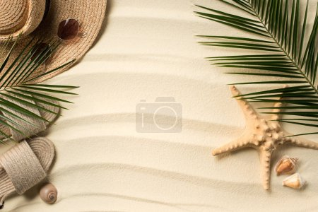 Photo for Flat lay with palm leaves, straw hat and flip flops on sandy beach - Royalty Free Image