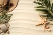 """Постер, картина, фотообои """"плоские лежит на пальмовых листьях, соломенной шляпе и флип-флоп на песчаном пляже"""""""
