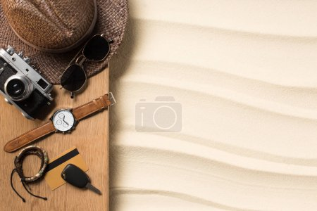 Photo for Flat lay with male accessories for traveling on wooden plank on sandy beach - Royalty Free Image