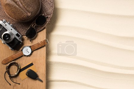 flat lay with male accessories for traveling on wooden plank on sandy beach