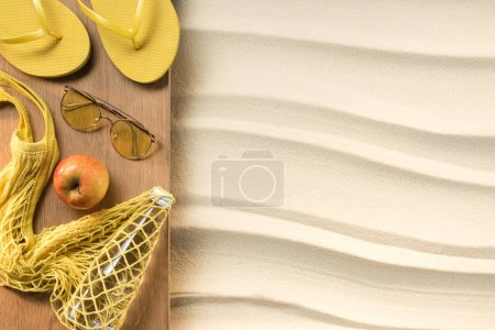flat lay with feminine yellow accessories for rest on beach on sand