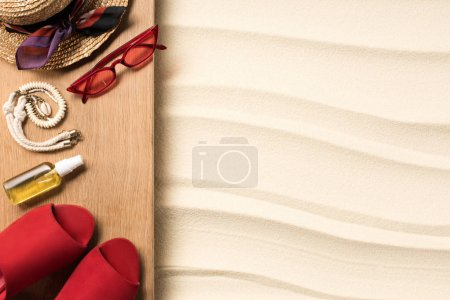 flat lay with feminine red accessories for rest on beach on sand