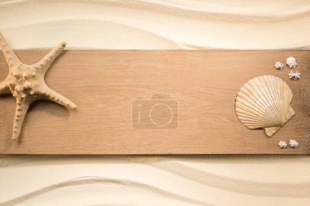 flat lay with arrangement of sea star and seashells on wooden plank on sand