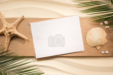 Photo pour Pose plate avec feuilles de palmier, papier blanc, étoile de mer et coquillages sur planche de bois sur sable - image libre de droit