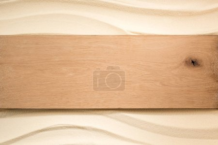 top view of blank wooden plank on sandy surface