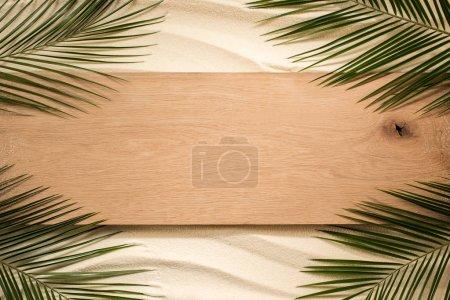 Photo pour Vue de dessus des feuilles de palmier et de la planche de bois sur une surface sablonneuse - image libre de droit