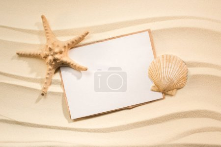 flat lay with sea star, seashell and blank paper on sand