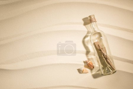 flat lay with paper roll in glass bottle and seashells on sand
