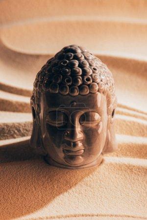 close up view of buddha sculpture on sandy beach