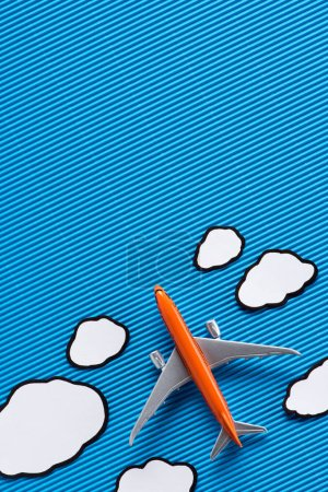 top view of toy plane and paper clouds on blue backdrop, trip concept