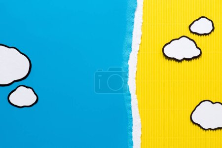 top view of paper clouds on blue and yellow paper background