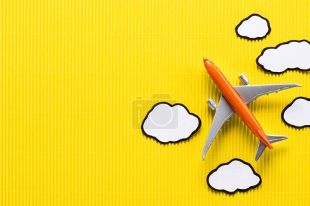 top view of toy plane and paper clouds on yellow background, trip concept