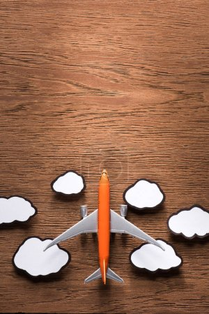 top view of toy plane and paper clouds on wooden surface, traveling concept