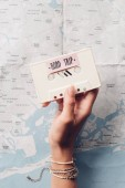 Cropped shot of woman holding retro audio cassette with map on background, road trip concept