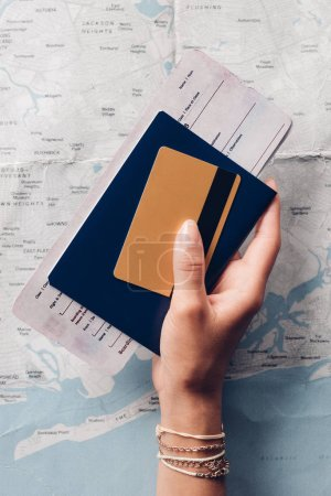 cropped shot of woman holding passport, ticket and credit card in hand with map on background, vacation concept