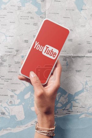 partial view of woman holding smartphone with youtube logo on screen and map on background