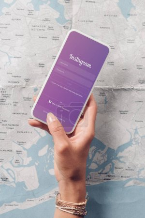 Photo for Partial view of woman holding smartphone with instagram logo on screen and map on background - Royalty Free Image