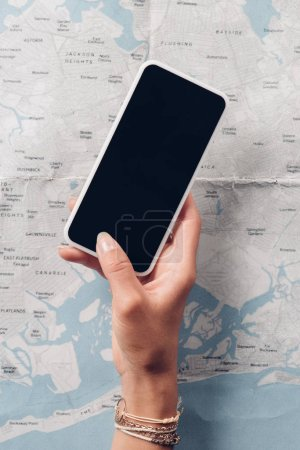 partial view of woman holding smartphone with blank screen with map on background, trip concept