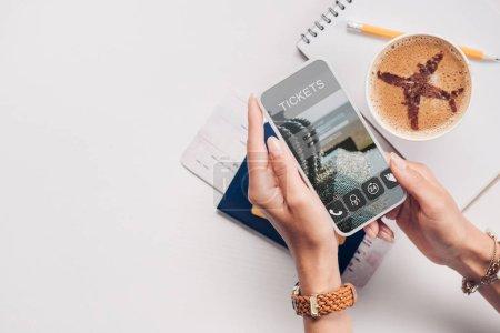 Photo pour Plan recadré de la femme avec smartphone avec le site Web des billets à l'écran à la table avec tasse de café, billet et passeport - image libre de droit