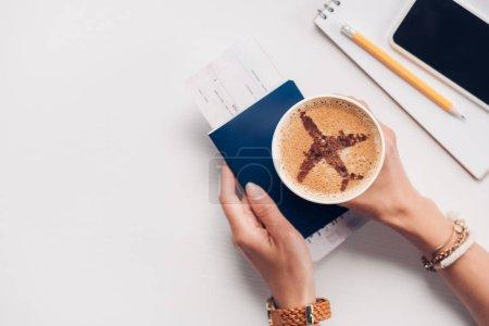 Photo pour Plan recadré de femme tenant une tasse de café avec panneau d'avion sur la table avec passeport, smartphone et billet, concept de voyage - image libre de droit