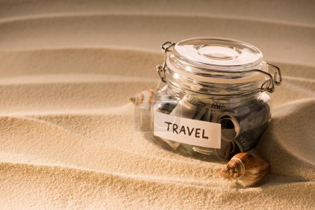close up view of glass jar with dollars on sandy beach with seashells, traveling concept
