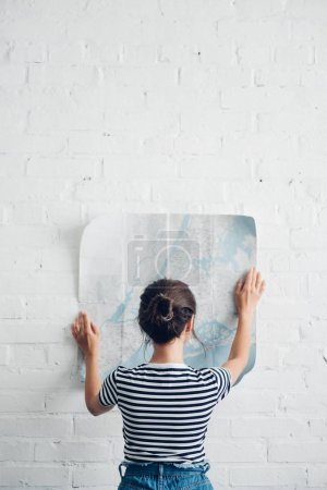 rear view of woman looking at map in hands at white brick wall, traveling concept