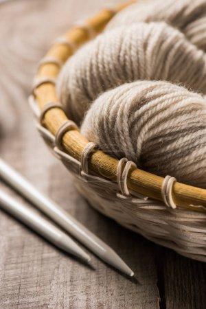 selective focus of beige knitted woolen yarn in wicker basket near knitted needles on wooden background
