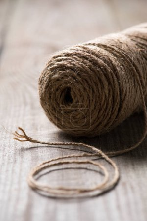 selective focus of untangled beige string on wooden background