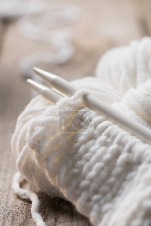 selective focus of knitted needles and white woolen knitted yarn