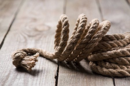 selective focus of beige knotted nautical rope on wooden background