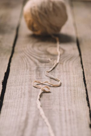 selective focus of untangled beige knitted yarn ball on wooden background