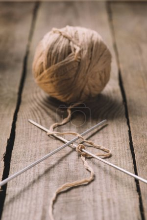 selective focus of beige knitted woolen yarn ball and knitted needles on wooden background