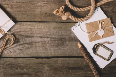 top view blank textbook, wrapped letter, tree pencil and nautical rope on wooden background