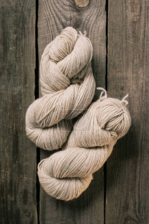 elevated view of two woolen beige knitting yarn balls on wooden background