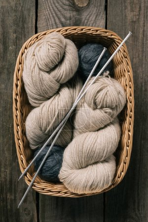 top view of beige and grey knitting yarn wit knitting needles in wicker basket on wooden background
