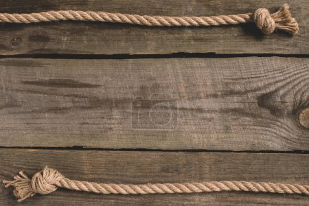 top view of beige knotted nautical rope on wooden background
